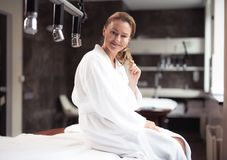 Joyful middle aged woman sitting on daybed at spa salon stock image