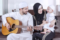 Joyful middle eastern family playing guitar royalty free stock photography