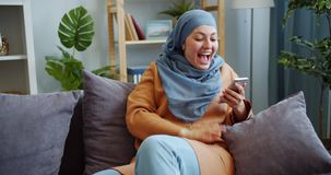 Joyful Middle Eastern girl in hijab using smartphone laughing having fun at home stock video