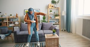 Joyful Middle Eastern woman in hijab dancing at home with headphones smartphone stock footage