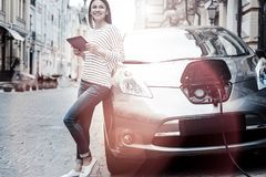 Joyful millennial girl using tablet while charging her electric car. Conserving energy future. Positive minded young brunette smiling cheerfully while leaning on Royalty Free Stock Images