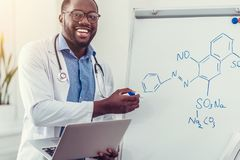 Joyful millennial medical professional pointing toward chemical formula. Positivity is the key to success. Excited young doctor smiling cheerfully while standing Royalty Free Stock Photos