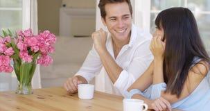 Joyful mixed adult couple sitting at table Royalty Free Stock Photography