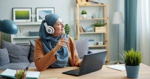 Mixed race girl in hijab enjoying music in headphones using laptop at home. Joyful mixed race girl in hijab is enjoying music in headphones using laptop at home stock footage