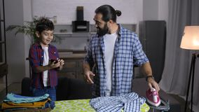 Single handsome father ironing clothes at home. Joyful mixed race son showing his success in video game on smart phone to his beloved bearded father while stay stock video