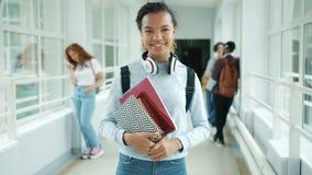 Joyful mixed race teenager holding books standing in college hallway smiling. Joyful mixed race teenager girl is holding books standing in college hallway stock footage