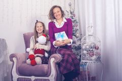 Joyful mom and daughter are sitting with presents. In front of a Christmas tree and having fun, in anticipation of the merry Christmas Royalty Free Stock Image