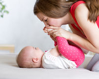 Joyful mom playing with her baby infant Stock Image