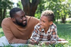 Delighted nice man smiling to his son. Joyful mood. Delighted nice men smiling to his son while lying with him on the grass stock photos