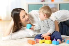 Joyful mother and baby playing on a carpet royalty free stock photography