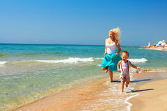 Joyful mother and baby running in surf on the beach Royalty Free Stock Photo