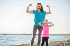 Joyful mother and daughter in fitness gear on beach flexing arms Stock Images