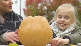 Joyful mother and daughter making jack lantern giving high-five, happiness. Stock footage stock footage