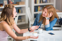 Joyful mother and daughter sitting at the table Royalty Free Stock Photography