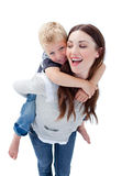 Joyful mother giving her son piggyback ride Royalty Free Stock Photo