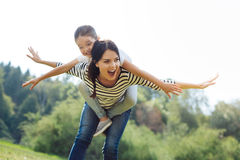 Joyful mother giving a piggyback to her little daughter Stock Photos