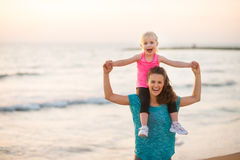 Joyful mother holding daughter on shoulders on beach at sunset Royalty Free Stock Photography