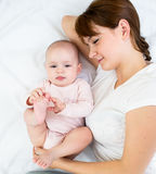 Joyful mother looking at her baby infant Stock Images