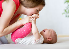 Joyful mother playing with baby infant Stock Images