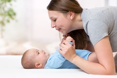 Joyful mother playing and doing gymnastics her baby infant Stock Photography