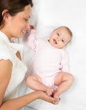 Joyful mother playing with her baby girl infant stock photo