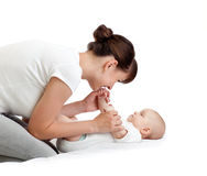 Joyful mother playing with her baby infant stock photography