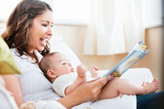 Joyful mother reading a book for her son Royalty Free Stock Photos