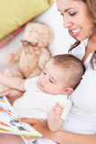 Joyful mother reading a book to her baby Stock Photo