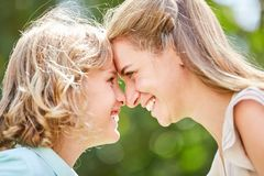 Mother and son look each other in the eye. Joyful mother and son look deep into each other`s eyes outdoors stock images