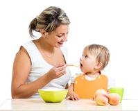Joyful mother spoon feeding her baby girl Royalty Free Stock Images
