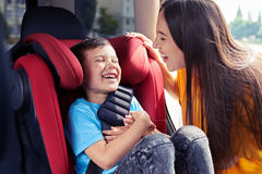 Joyful mother tickling son sitting in baby seat. Mid shot of joyful mother tickling son sitting in baby seat Royalty Free Stock Photography