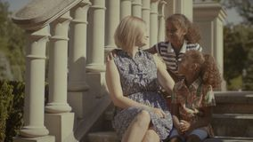 Joyful multi ethnic family resting on stairs. Joyful loving diverse family with two elementary age mixed race girls resting and chatting while sitting on stairs stock footage