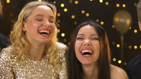 Joyful multiethnic friends blowing on golden confetti, having fun at xmas party. Stock footage stock footage