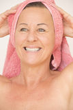 Joyful naked mature woman with towel Royalty Free Stock Image