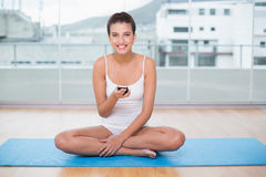 Joyful natural brown haired woman in white sportswear texting with her mobile phone Stock Image