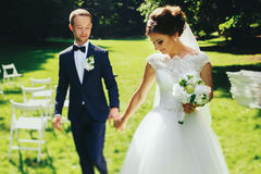 Joyful newlyweds walk in the garden full of sun Stock Image
