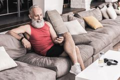 Positive senior male using mobile phone while relaxing in gym royalty free stock image