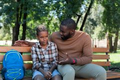 Joyful nice afro american man talking to his son. Fathers advice. Joyful nice men talking to his son while being with him in the park royalty free stock photography
