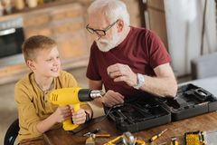 Joyful nice boy helping his grandfather. Male skills. Joyful nice positive boy sitting next to his grandfather and holding a drill while helping him Royalty Free Stock Photos