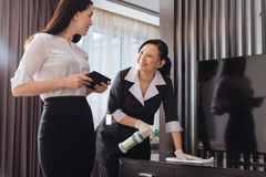 Joyful nice businesswoman talking to a hotel maid. Hotel service. Joyful nice positive businesswoman standing near a hotel maid and talking to her while holding Stock Image