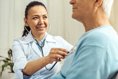 Joyful nice doctor doing medical examination. Medical auscultation. Joyful nice female doctor holding a stethoscope and pressing it to her patients chest while royalty free stock photos