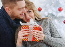 Joyful nice girl in the arms of a boyfriend with christmas gifts royalty free stock photography