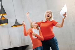Joyful nice grandmother and granddaughter feeling happy. We did it. Joyful nice delighted grandmother and granddaughter laughing and expressing their emotions Royalty Free Stock Photo
