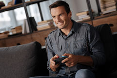 Joyful nice guy enjoying his hobby at home. Weekend activities. Young attractive passionate man sitting on a couch and holding a controller while playing video Stock Photos