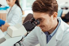 Joyful nice man being happy about the research. Positive results. Joyful nice men looking into the microscope while being happy about his research royalty free stock image
