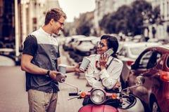Joyful nice man offering coffee to his girlfriend royalty free stock photo