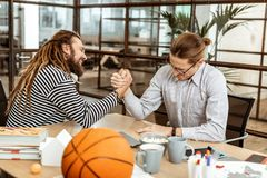 Joyful nice men deciding who is stronger. Male activity. Joyful nice men deciding who is stronger while having a lunch break in the office royalty free stock images