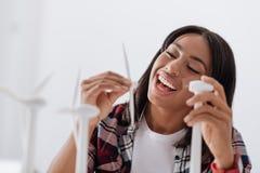 Joyful nice woman constructing a windmill model. Environmental engineer. Joyful nice delighted woman sitting at the table and constructing a windmill model while Stock Photos