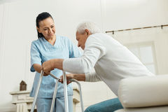 Joyful nice woman helping an elderly man. Professional caregiver. Joyful nice pleasant women smiling and looking at the elderly men while helping him to walk Stock Images
