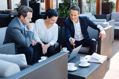 Joyful nice woman sitting with her business partners Royalty Free Stock Images